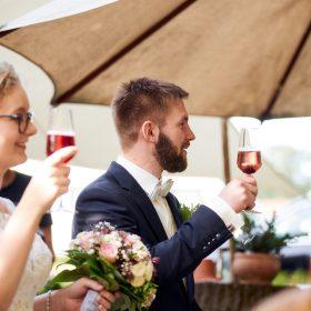 Das Brautpaar hebt die rot gefüllten Sektgläser im Garten der Location - Hof Wietfeldt Bennebostel © Hochzeitsfotograf www.hochzeitsverliebt.de