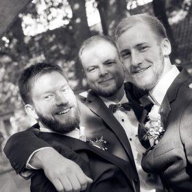 Schwarzweissbild vom Bräutigam im Sommer mit seinen zwei Freunden im Freien - Hof Wietfeldt Bennebostel © Hochzeitsfotograf www.hochzeitsverliebt.de