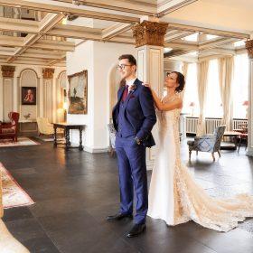 Die Braut steht hinter ihrem Bräutigam im barocken Foyer kurz vor dem First Look - Celle Althoff Hotel Fürstenhof © Hochzeitsfotograf www.hochzeitsverliebt.de