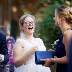 Herzhaft lachende Braut während der Gratulationen ihrer Gäste - Hof Wietfeldt Bennebostel © Hochzeitsfotograf www.hochzeitsverliebt.de