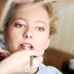 Braut sieht verträumt in die Ferne, während ihr rosa Lippenstift aufgetragen wird - Hof Wietfeldt Bennebostel © Hochzeitsfotograf www.hochzeitsverliebt.de