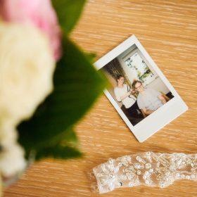 Detail vom Brautstrauß mit Polaroidaufnahme auf hellen Holztisch und Spitzenband - Hof Wietfeldt Bennebostel © Hochzeitsfotograf www.hochzeitsverliebt.de