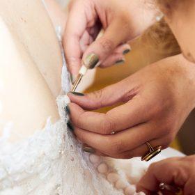 Der weiss gekleideten Braut wird im Rücken das Kleid geknöpft von vier helfenden Händen - Hof Wietfeldt Bennebostel © Hochzeitsfotograf www.hochzeitsverliebt.de