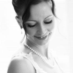 Schwarzweissbild der lächelnden Braut mit Blick nach unten als Hochzeitsporträt - Celle Althoff Hotel Fürstenhof © Hochzeitsfotograf www.hochzeitsverliebt.de