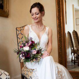 Sitzende Braut mit rosafarbenem Brautstrauß schaut lächend zu ihrem Strauß und spiegelt sich im Barockspiegel von hinten - Celle Althoff Hotel Fürstenhof © Hochzeitsfotograf www.hochzeitsverliebt.de