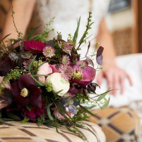 Hochzeitsbild vom liegenden Brautstrauß auf dem hellen Stoffstuhl mit der sitzenden Braut im Hintergrund in Unschärfe - Celle Althoff Hotel Fürstenhof © Hochzeitsfotograf www.hochzeitsverliebt.de