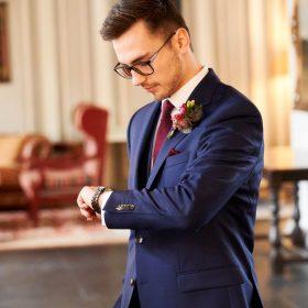 Bräutigam im blauen Anzug wartet im Foyer mit Blick auf die Armbanduhr auf seine Braut - Celle Althoff Hotel Fürstenhof © Hochzeitsfotograf www.hochzeitsverliebt.de