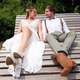 Entspannung für das Brautpaar auf der grauen Holzliege im Park - Winsen Aller © Hochzeitsfotograf www.hochzeitsverliebt.de