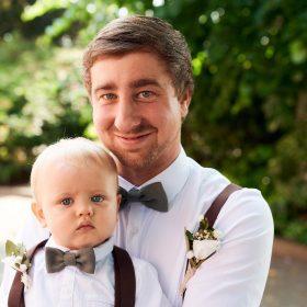Bräutigam hält seinen Sohn auf dem Arm und beide schauen in die Kamera - Standesamt Winsen Aller © Hochzeitsfotograf www.hochzeitsverliebt.de