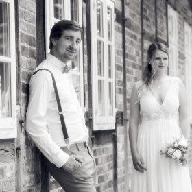 Schwarzweissfoto vom Brautpaar am Fachwerk - Standesamt Winsen Aller © Hochzeitsfotograf www.hochzeitsverliebt.de