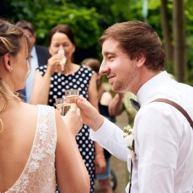 Braut und Bräutigam stoßen draussen inmitten von Gästen mit Sekt an - Standesamt Winsen Aller © Hochzeitsfotograf www.hochzeitsverliebt.de