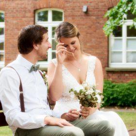 Vertrauter Moment vom Brautpaar auf der braunen Parkbank - Kirchengarten Winsen Aller © Hochzeitsfotograf www.hochzeitsverliebt.de
