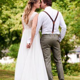 Das Hochzeitspaar steht Hände haltend im Park und küsst sich - Kirchengarten Winsen Aller © Hochzeitsfotograf www.hochzeitsverliebt.de