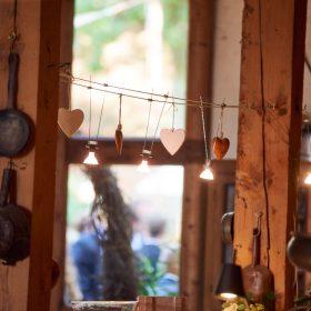 Zwischen zwei Holzsäulen gespannte Schnur mit Lichtern und Herzen in de Hochzeitslocation - Hof Wietfeldt Bennebostel © Hochzeitsfotograf www.hochzeitsverliebt.de