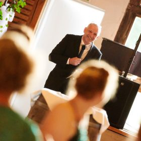 Gäste schauen zum Redner mit Mikrofon - Hof Wietfeldt Bennebostel © Hochzeitsfotograf www.hochzeitsverliebt.de