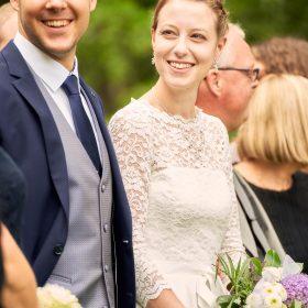 Lächelndes Brautpaar in der Menge der Gäste in der grünen Natur  - Junkerhof Wittingen © Hochzeitsfotograf www.hochzeitsverliebt.de