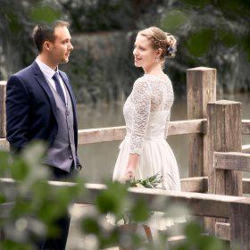 Lächelndes Brautpaar in der Natur mit grünen und unscharfen Blättern im Vordergrund - Junkerhof Wittingen © Hochzeitsfotograf www.hochzeitsverliebt.de
