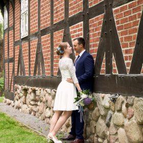 Das Brautpaar lehnt am roten Fachwerkhaus mit hellem Steinsockel und lächelt sich an - Junkerhof Wittingen © Hochzeitsfotograf www.hochzeitsverliebt.de