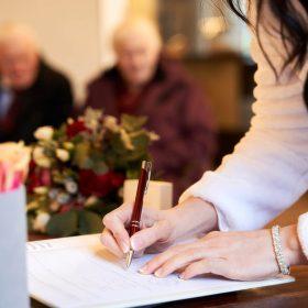 Die Braut unterschreibt die Eheschliessung mit einen rotem Stift - Trauzimmer Schlösschen Bad Nenndorf © Hochzeitsfotograf www.hochzeitsverliebt.de