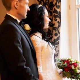Braut in weiss schmiegt sich an ihren Bräutigam, der sie am Fenster in seinen Armen hält - Schlösschen Bad Nenndorf © Hochzeitsfotograf www.hochzeitsverliebt.de