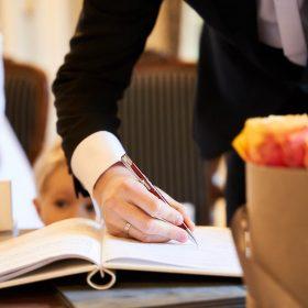Unterschrift des Bräutigams von der Eheschliessung mit dem roten Stift - Schlösschen Bad Nenndorf © Hochzeitsfotograf www.hochzeitsverliebt.de
