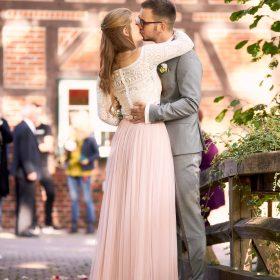 Küssendes Brautpaar auf der Brücke mit Gästen im Hintergrund - Trauinsel Wienhausen © Hochzeitsfotograf www.hochzeitsverliebt.de