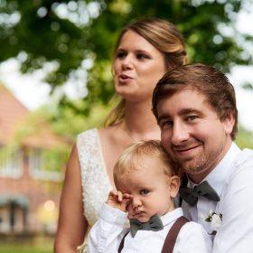 Das Hochzeitspaar mit ihrem Sohn unterm grünen Baum mit Fachwerkhaus im unscharfen Hintergrund - Kirchengarten Winsen Aller © Hochzeitsfotograf www.hochzeitsverliebt.de