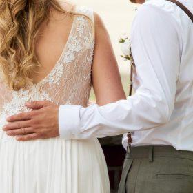 Der Bräutigam legt seine Hand an den Rücken seiner weiss gekleideten Braut mit Rückenausschnitt - Kirchengarten Winsen Aller