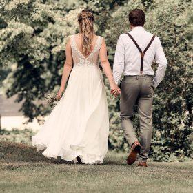 Rückansicht vom Spaziergang des Brautpaares durch den Garten - Kirchengarten Winsen Aller © Hochzeitsfotograf www.hochzeitsverliebt.de