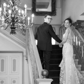 Braut und Bräutigam schreiten die barocke Treppe herauf als Schwarzweissfoto - Celle Althoff Hotel Fürstenhof © Hochzeitsfotograf www.hochzeitsverliebt.de