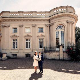 Schloss Richmond im Sonnenschein mit Brautpaar im Vordergrund- Schloss Richmond Braunschweig © Hochzeitsfotograf www.hochzeitsverliebt.de