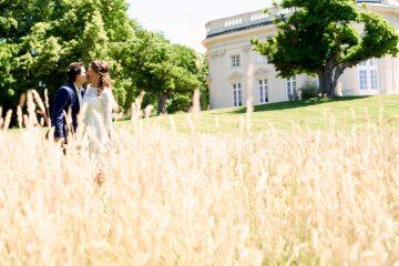 Das Brautpaar küsst sich bei Sonnenschein im hohen Gras mit Schloss im Hintergrund - Schloss Richmond Braunschweig © Hochzeitsfotograf www.hochzeitsverliebt.de
