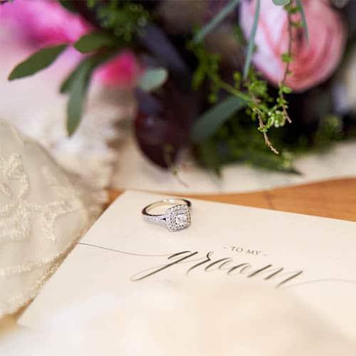 Brief der Braut an den Bräutigam in creme und silberner Schrift sowie silbernem Ring mit Diamanten und Brautstrauß in Rosatönen - Celle © Hochzeitsfotograf www.hochzeitsverliebt.de