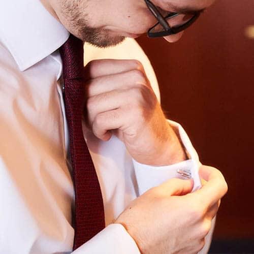Bräutigam im Detail und weinroter Krawatte steckt an seinem weisse Hemd einen Manschettenknopf am linken Ärmel - Celle © Hochzeitsfotograf www.hochzeitsverliebt.de