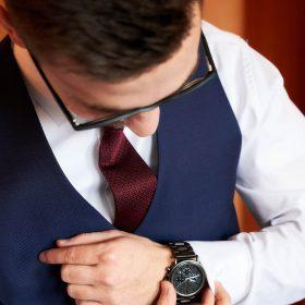 Bräutigam in blauer Weste mit roter Krawatte und weissem Hemd schaut auf seine Armbanduhr - Celle Ringhotel Celler Tor © Hochzeitsfotograf www.hochzeitsverliebt.de