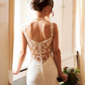 Braut mit Hochsteckfrisur im cremefarbenem Brautkleid mit Rückenausschnitt und Spitze steht am Fenster im hellen Raum - Celle Althoff Hotel Fürstenhof © Hochzeitsfotograf www.hochzeitsverliebt.de