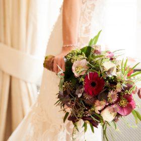 Detail der Baut im Kleid aus Spitze und Stickerei mit ihrem Brautstrauß in der rechten Hand - Celle Althoff Hotel Fürstenhof © Hochzeitsfotograf www.hochzeitsverliebt.de