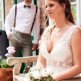 Der Bräutigam am roten Fachwerkhaus lehnend mit seiner Braut auf der Bank im Vordergrund - Standesamt Winsen Aller © Hochzeitsfotograf www.hochzeitsverliebt.de