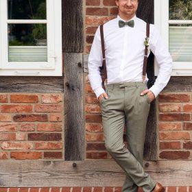Lässig lehnender Bräutigam mit Hosenträgern am roten Fachwerk mit weissen Fenstern - Standesamt Winsen Aller © Hochzeitsfotograf www.hochzeitsverliebt.de