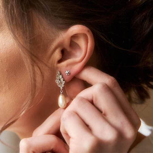 Braut im Detailprofil und Hochsteckfrisur steckt sich einen Ohrring ans linke Ohr- Celle © Hochzeitsfotograf www.hochzeitsverliebt.de