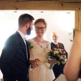 Der Bräutigam führt die Braut durch die Scheune zum Trautisch - Hof Wietfeldt Bennebostel © Hochzeitsfotograf www.hochzeitsverliebt.de