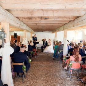 Sitzende Hochzeitsgesellschaft mit dem Brautpaar in der hellen Holzscheune - Hof Wietfeldt Bennebostel © Hochzeitsfotograf www.hochzeitsverliebt.de