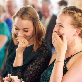 Lachende junge und sitzende Frauen während der Trauung in der Scheune - Hof Wietfeldt Bennebostel © Hochzeitsfotograf www.hochzeitsverliebt.de
