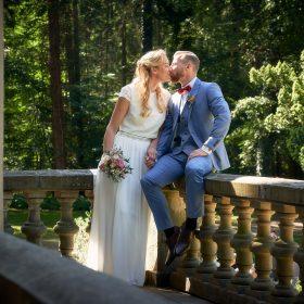 Bräutigam sitzt auf der Balustrade aus hellem Stein und küsst seine stehende Braut in weiss - Schloss Eldingen © Hochzeitsfotograf www.hochzeitsverliebt.de