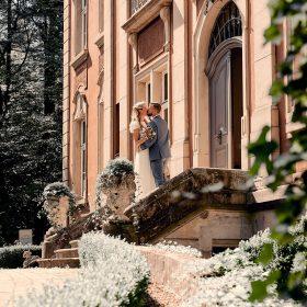 Das Brautpaar küsst sich am opulenten Schlosseingang - Schloss Eldingen © Hochzeitsfotograf www.hochzeitsverliebt.de