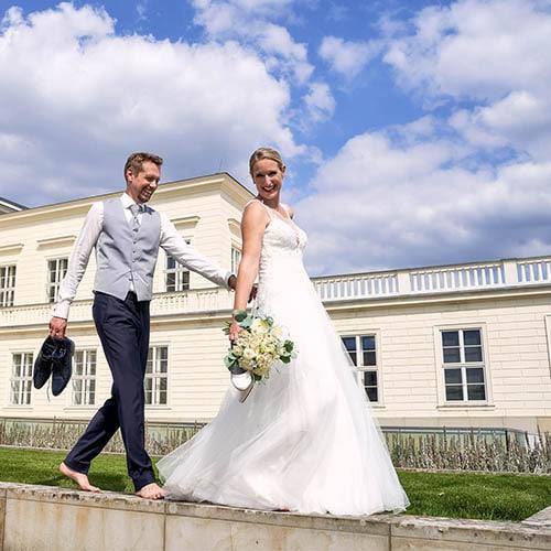 Brautpaar geht am Schloss barfuss auf Steinen unter bei blauem Himmel mit weissen Wolken - Herrenhäuser Gärten Hannover © Hochzeitsfotograf www.hochzeitsverliebt.de