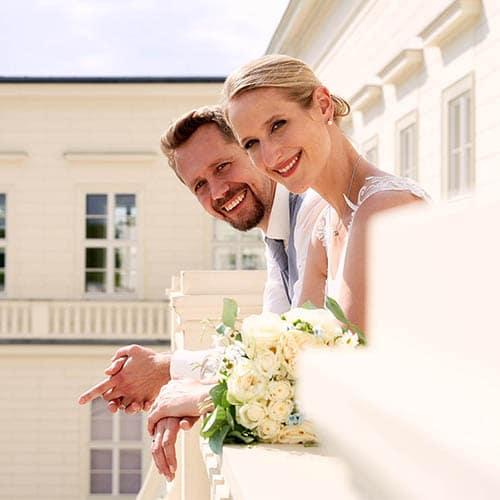 Braut und Bräutigam schauen über heller Schlossbalustrade in die Kamera- Herrenhäuser Gärten Hannover © Hochzeitsfotograf www.hochzeitsverliebt.de