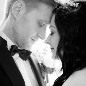 Schwarzweissbild vom Brautpaar, das Kopf an Kopf im Gegenlicht zueinander steht - Schlösschen Bad Nenndorf © Hochzeitsfotograf www.hochzeitsverliebt.de