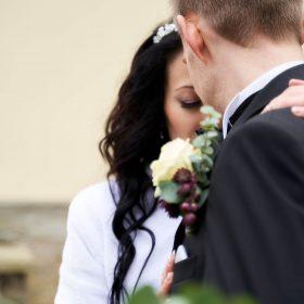 Braut und Bräutigam kuscheln vor gelber Fassade miteinander und halten einen rotgrünen Brautstrauß - Kurpark Bad Nenndorf © Hochzeitsfotograf www.hochzeitsverliebt.de