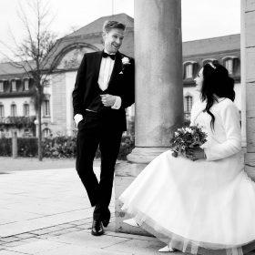 Schwarzweissbild vom Bräutigam, der vor dem stilvollen Gebäude an der Säule lehnt und zu seiner sitzenden Braut schaut - Kurpark Bad Nenndorf © Hochzeitsfotograf www.hochzeitsverliebt.de